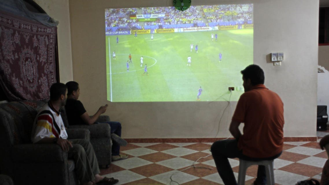 Palestinians watch a television projection of a live telecast displaying the the 2014 FIFA World Cup final between Argentina and Germany in Brazil, in the southern Gaza Strip town of Rafah on July 13, 2014. AFP