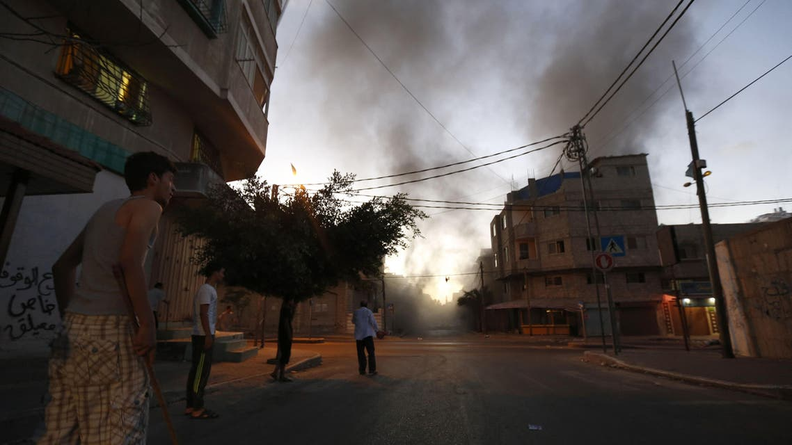 Palestinians stand looking at smoke billowing from a nearby building hit by an Israeli air strike in Gaza City on July 13, 2014. (AFP)