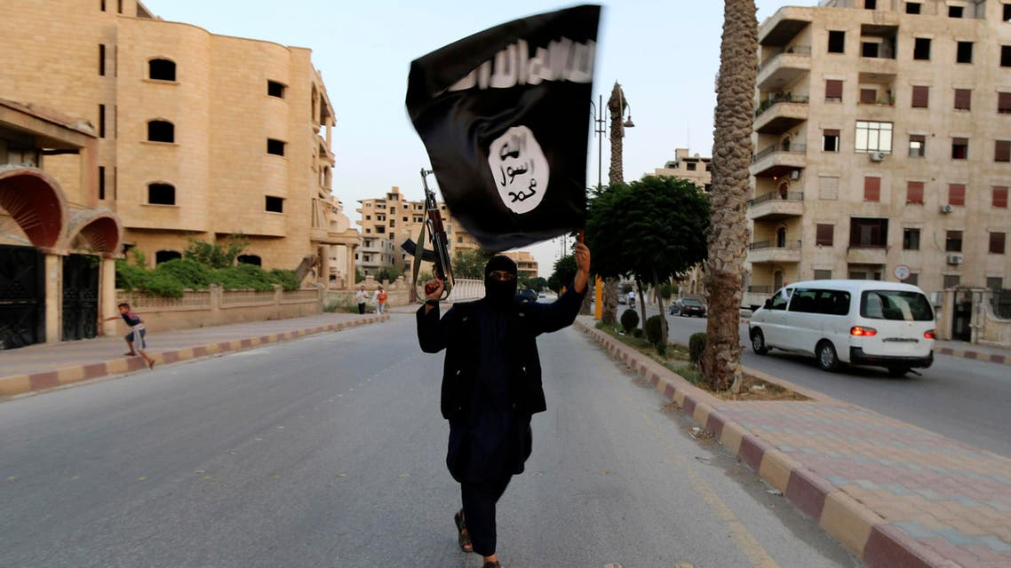 A member loyal to the Islamic State in Iraq and Syria (ISIS) waves an ISIS flag in Raqqa June 29, 2014. (Reuters)