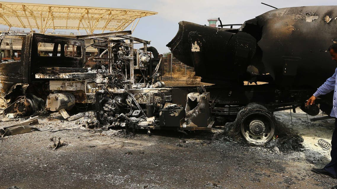 The wreckage of a truck and an airplane are seen at Tripoli international airport in the Libyan capital on July 14, 2014  afp
