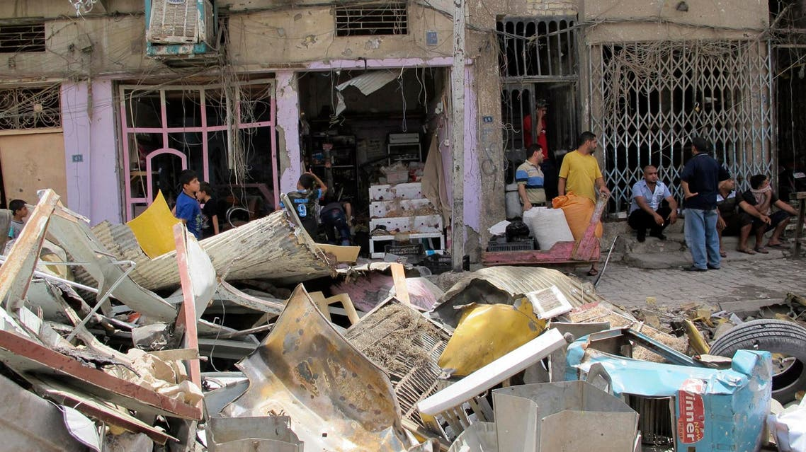 Residents look at the site of a car bomb attack in Baghdad July 14, 2014.