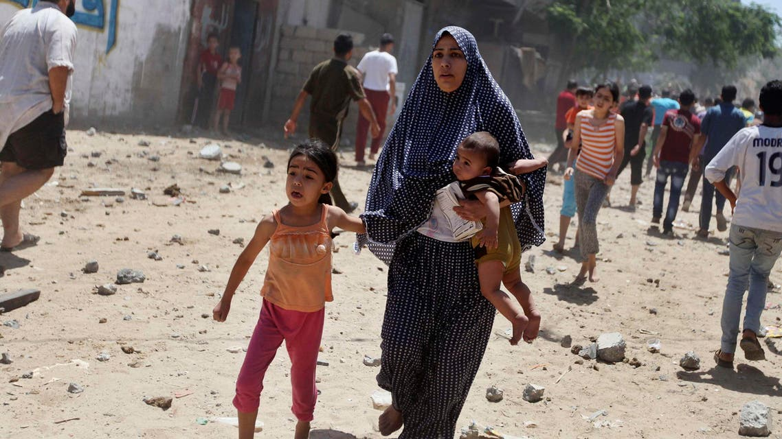 A Palestinian woman runs with her children following what police said was an Israeli air strike on a house in Gaza city July 9, 2014.