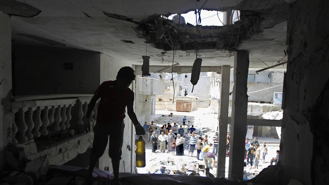 Palestinians search for goods through the rubble of a destroyed building belonging to a charity organization following an Israeli air strike in Rafah, in the southern Gaza Strip, on July 15, 2014.