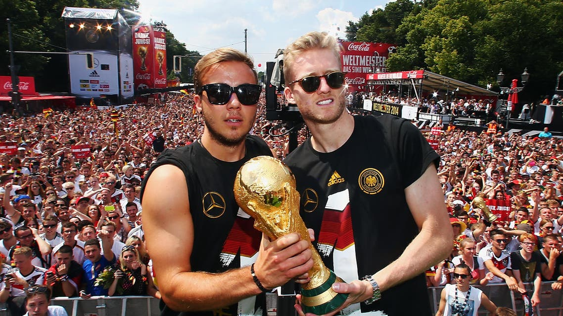 Germany's Mario Goetze (L) and Andre Schuerrle pose with the World Cup trophy during celebrations to mark the team's 2014 Brazil World Cup victory, at a 'fan mile' public viewing zone in Berlin July 15, 2014.