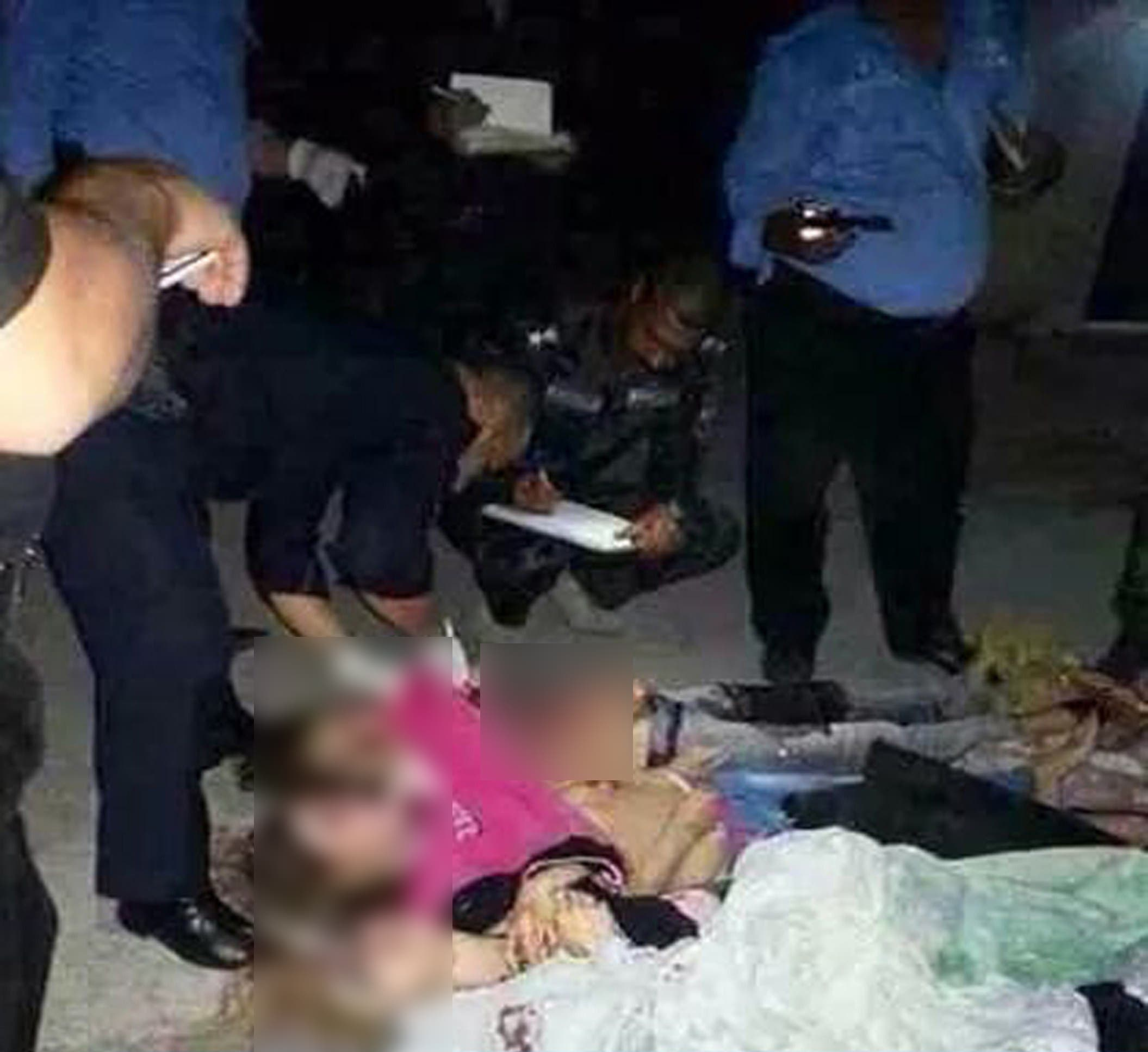 Iraqi security forces checking the bodies of alleged prostitutes after they were slaughtered by gunmen. (AFP)