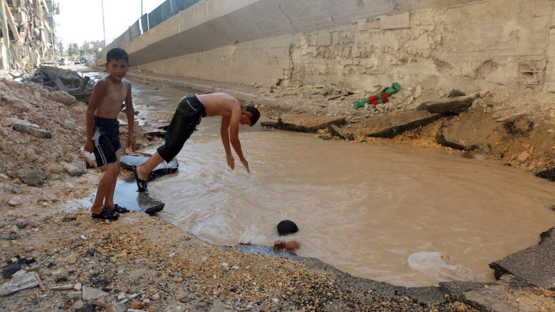 Syrian children play in a bomb crater flooded with water from a broken main in the northern city of Aleppo. (AFP)