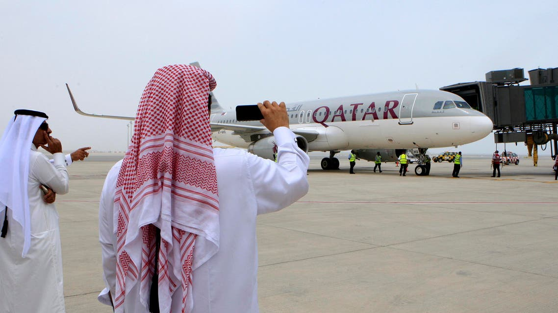 Qatari men take pictures after the Airbus A320-200 aircraft chartered by Qatar Airways landed at Doha's new Hamad International Airport