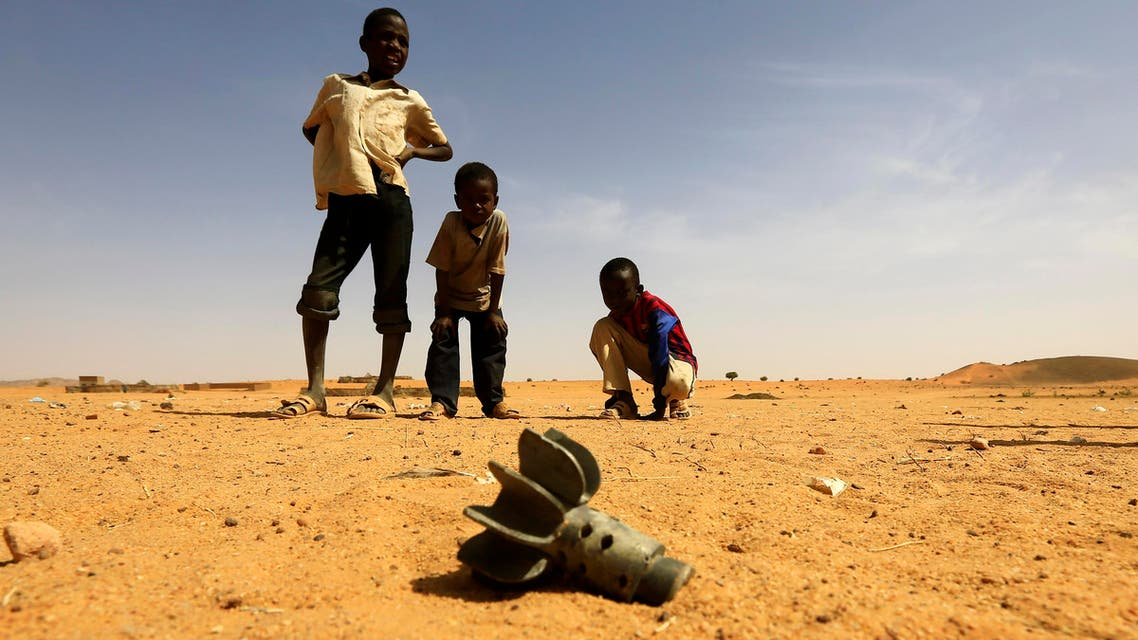 Children in Darfur examine a fallen mortar round