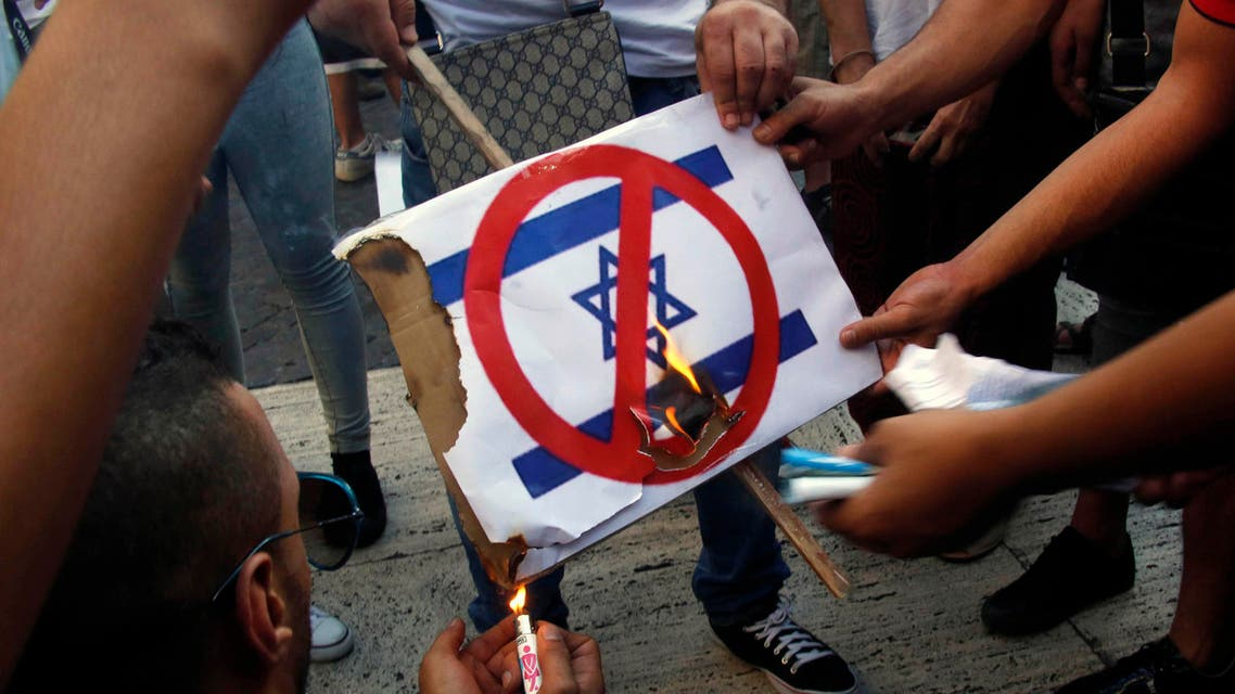 Demonstrators burn a placard with a picture of Israel's flag during a protest in Barcelona, against Israel's military action in Gaza, July 17, 2014.