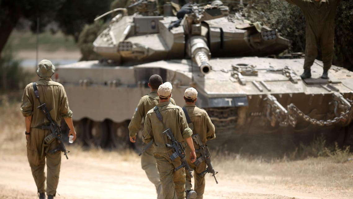 Israeli soldiers walk towards a Merkava tank, at an army deployment area near Israel's border with the Gaza Strip. (Reuters)