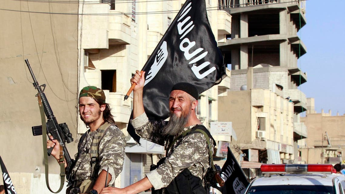 Militant Islamist fighters wave flags as they take part in a military parade along the streets of Syria's northern Raqqa province June 30, 2014. reuters