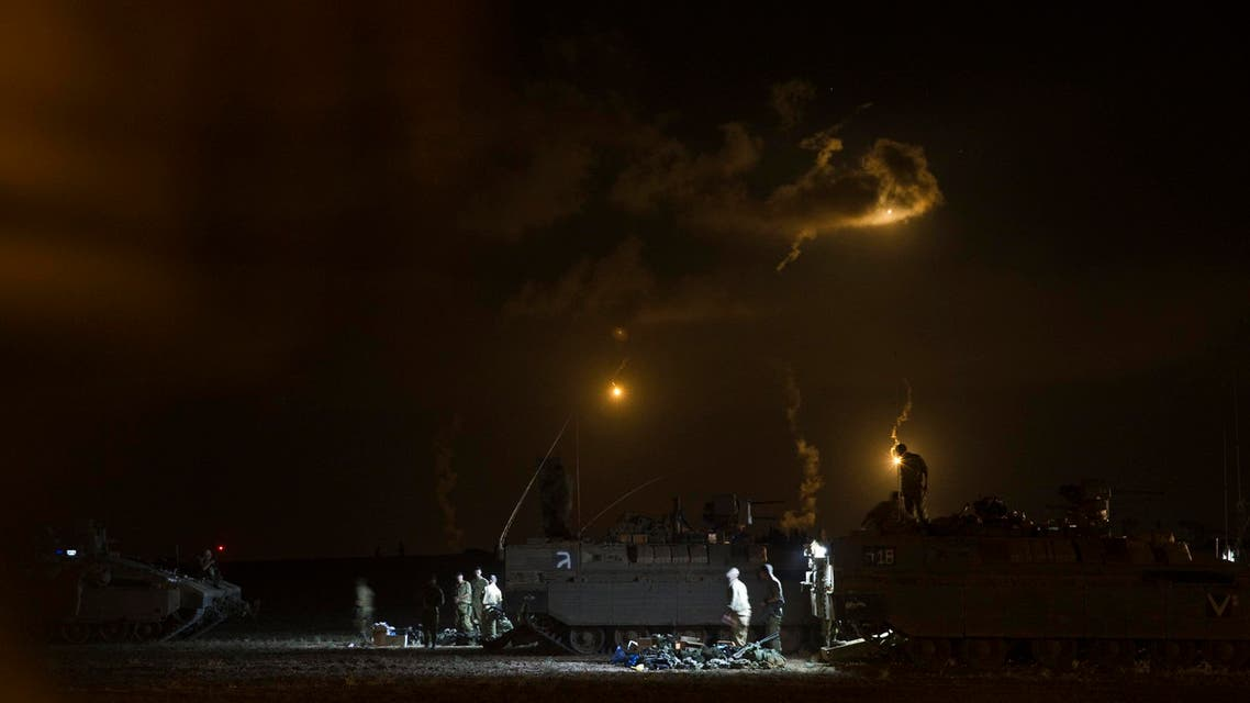 Israeli soldiers stand around their armoured personnel carriers (APCs) across from the northern Gaza Strip, as flares from Israel light the sky, July 18, 2014. (Reuters)