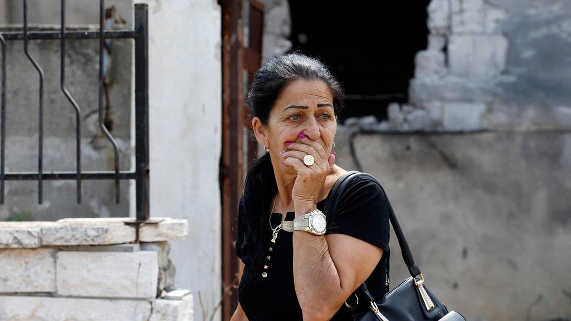 A woman reacts as she passes by a house damaged by a rocket, fired by Palestinian militants, that landed in the southern town of Sderot July 21, 2014. Reuters