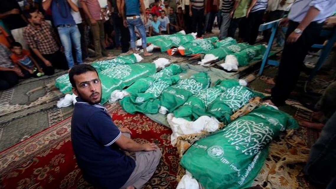 A man sits next to the bodies of Palestinians from Abu Jama'e family, who medics said were killed in an Israeli air strike that destroyed their house, during their funeral at a mosque in Khan Younis in the southern Gaza Strip July 21, 2014. (Reuters)