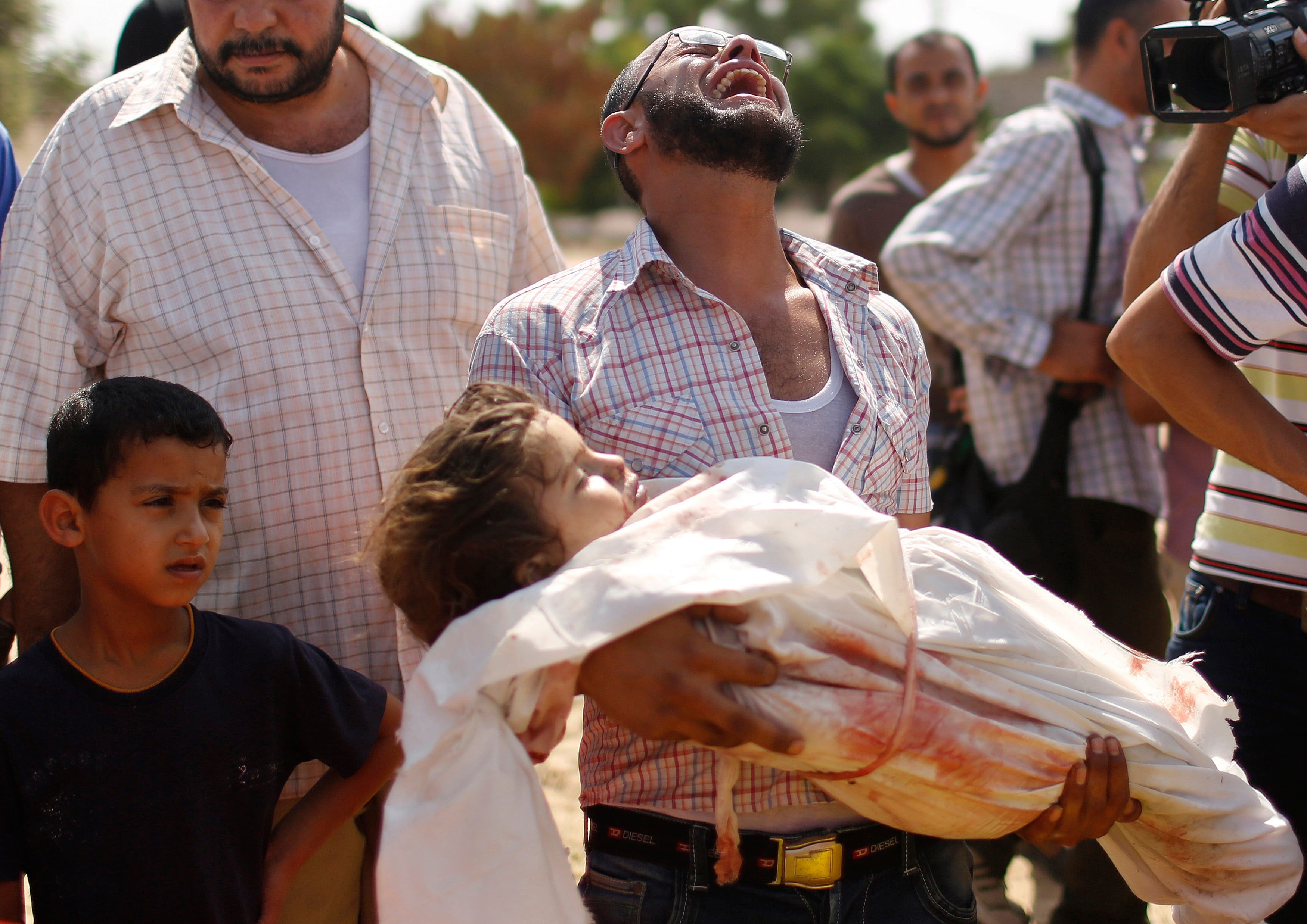relative cries as he carries the body of three-year-old Palestinian girl Haniyeh Abu Jarad, who medics said was killed along with her father and other six members from the same family by an Israeli tank shell, during their funeral in Beit Lahiya in the northern Gaza Strip July 19, 2014. (Reuters)