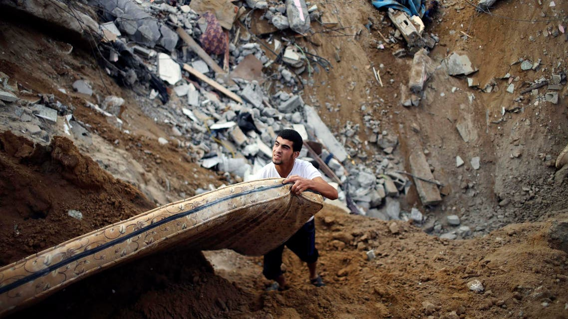 A Palestinian salvages a mattress from the remains of a house, which police said was destroyed in an Israeli air strike, in Khan Younis in the southern Gaza Strip July 21, 2014 reuters