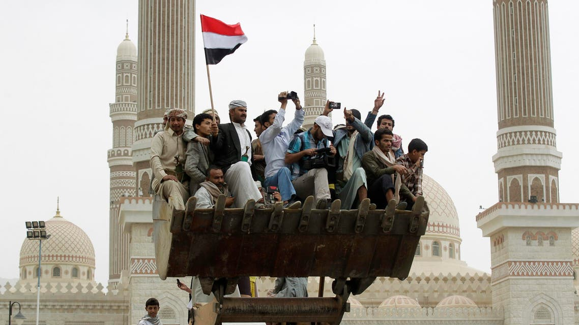 People ride on a bulldozer during the funeral of army commander Brigadier General Hameed al-Qushaibi in Sanaa July 23, 2014.  Reuters