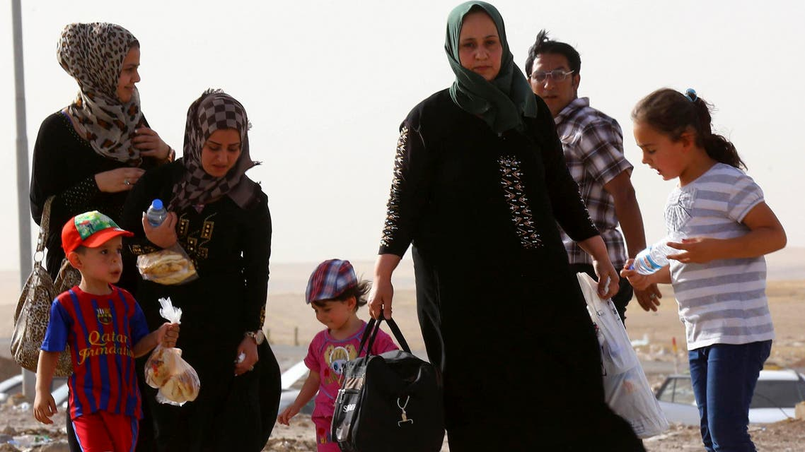 A family fleeing the violence in Mosul waits at a checkpoint on the outskirts of Arbil, in Iraq's Kurdistan region, June 11, 2014.  (Reuters)