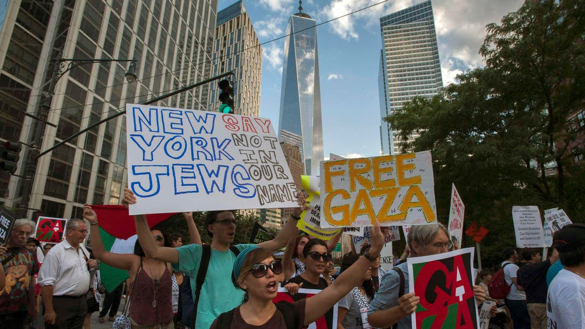 """One World Trade Center is seen in the background as activists hold placards while shouting """"Free, free Palestine"""" and """"Not another nickel, not another dime, no more money for Israel's crimes,"""" during a protest march through Lower Manhattan, New York July 24, 2014. Reuters"""