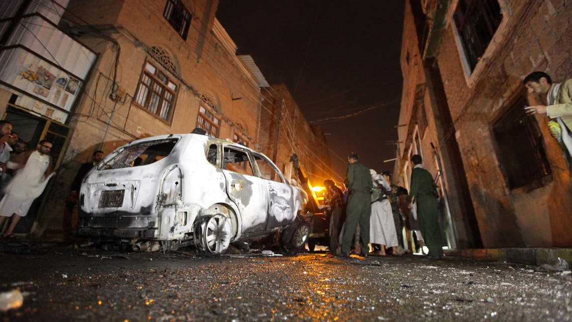 Policemen inspect the scene of a blast that destroyed the car of Abdullah al-Mutawakil, a senior security officer, outside his house in Sanaa early July 20, 2014. Reuters