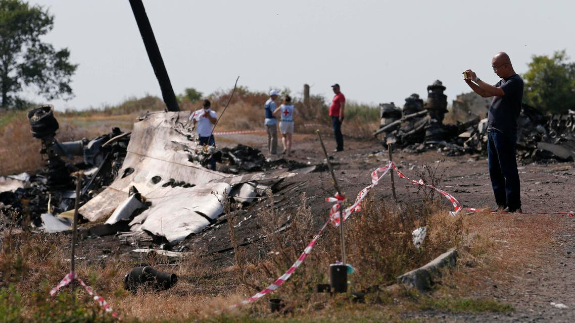 A Malaysian air crash investigator (R) works at a crash site of the Malaysia Airlines Flight MH17 near the village of Hrabove (Grabovo), Donetsk region July 24, 2014. Reuters