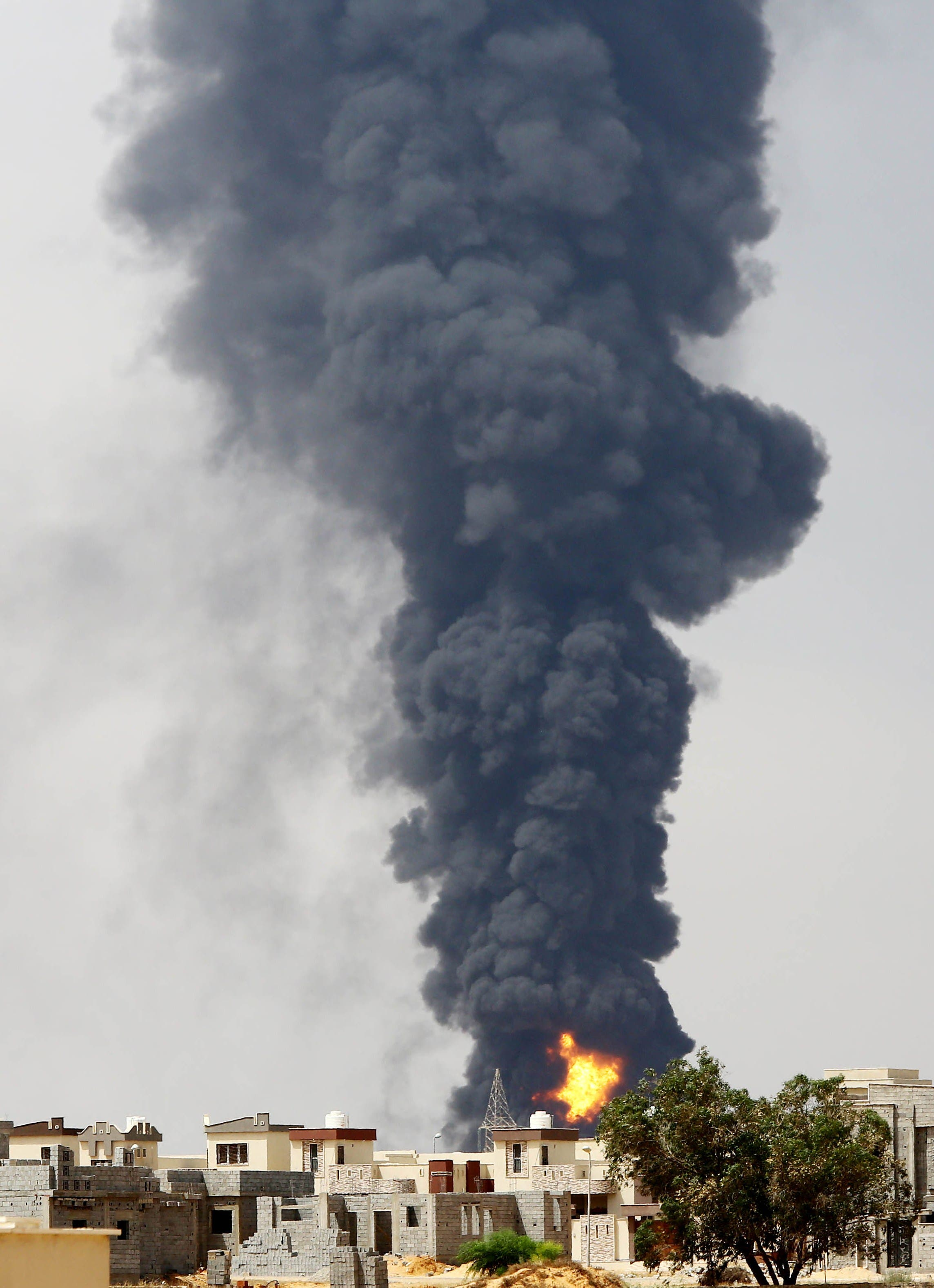 A picture taken on July 28, 2014 shows flames and smoke billowing from an oil depot where a huge blaze started following clashes around Tripoli airport, in southern Tripoli.  (AFP)