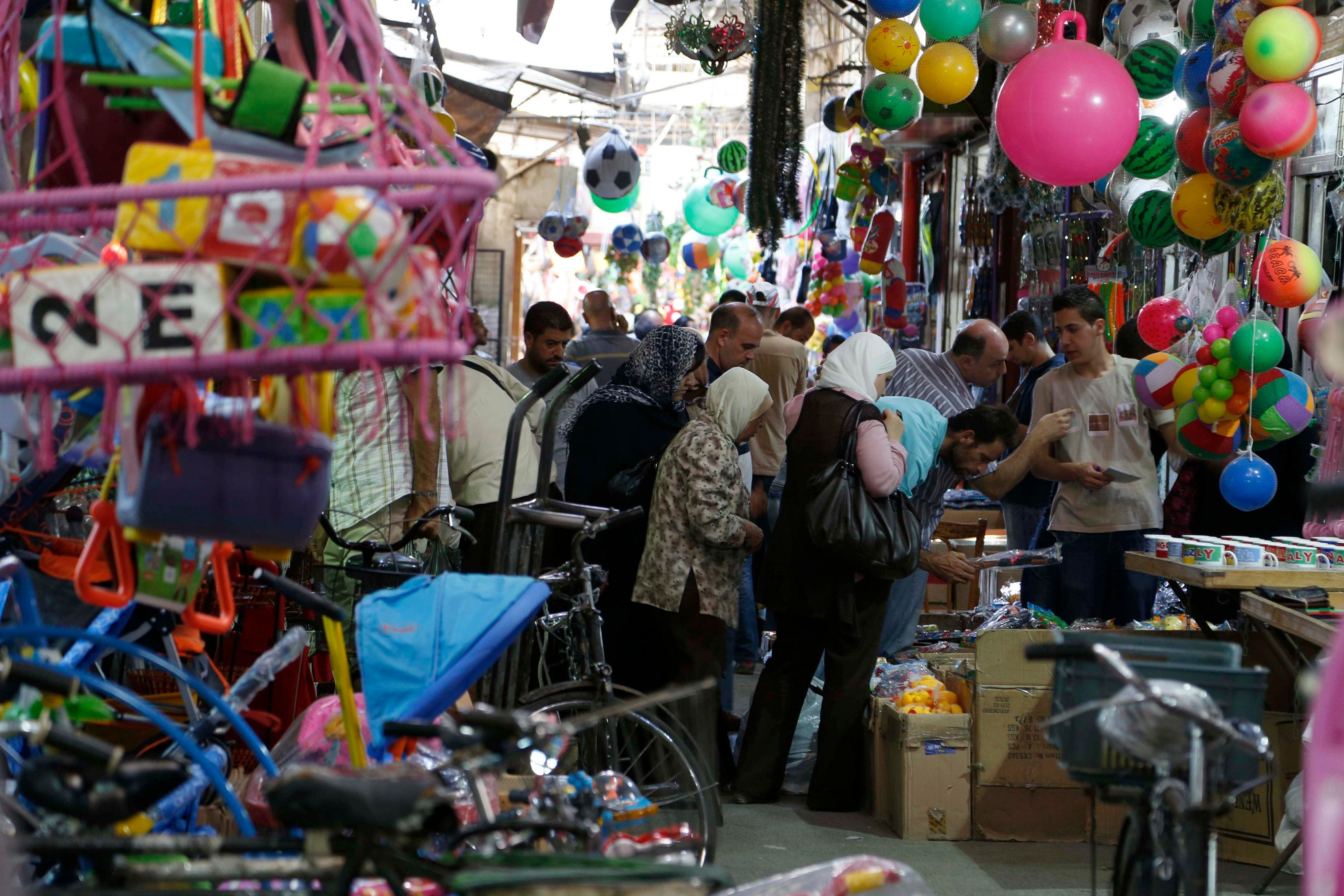 Residents inspect toys in Al-Asrouniyeh souk ahead of Eid al-Fitr celebrations in Damascus July 27, 2014. Reuters