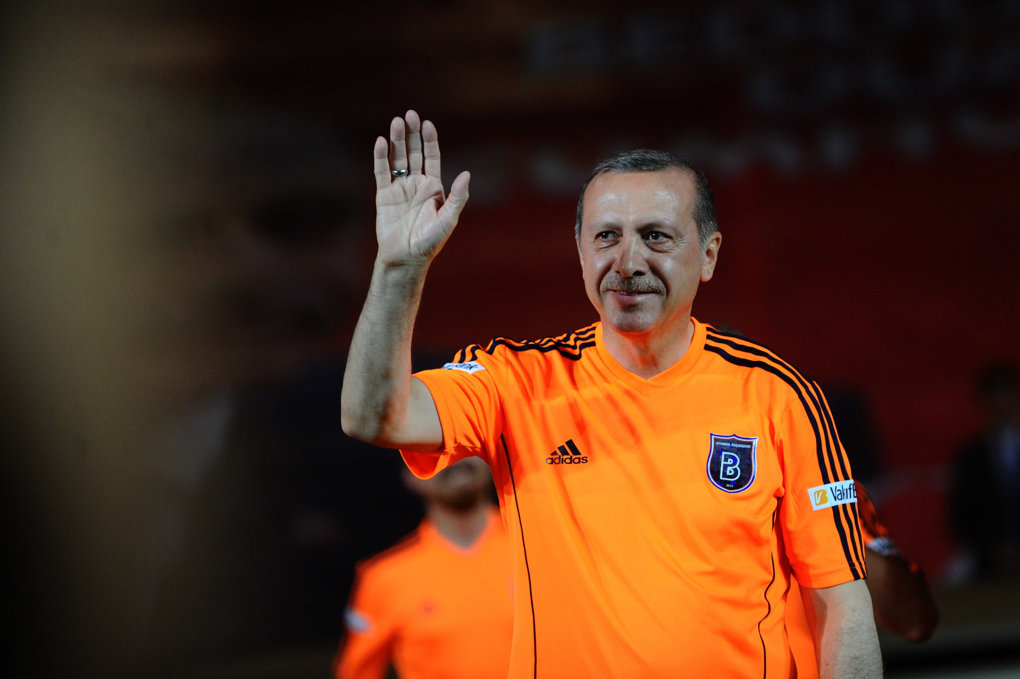 Turkish Prime Minister Recep Tayyip Erdogan waves to supporters during an exhibition match at the Basaksehir stadium on 26 July, 2014 in Istanbul. AFP