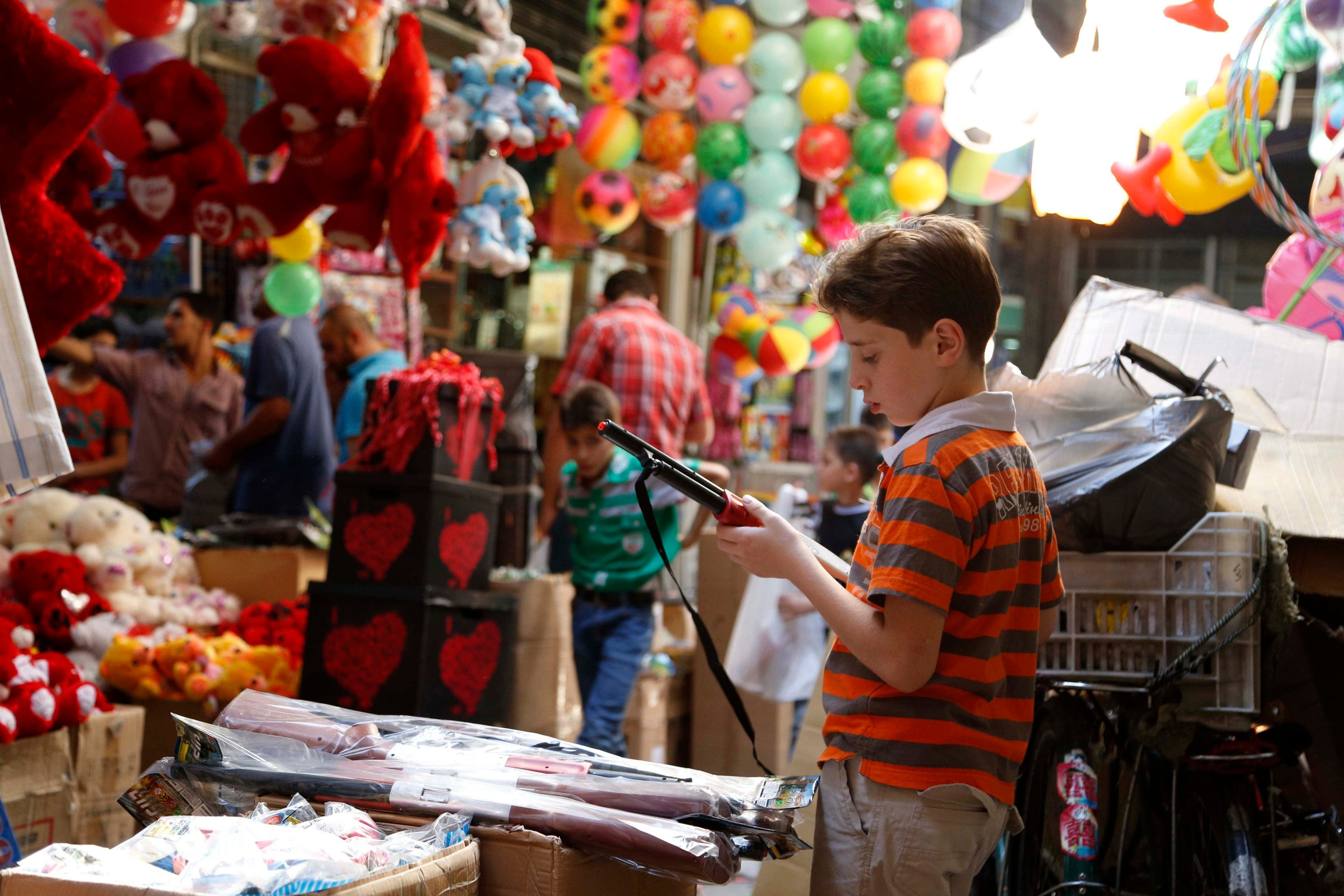 A child inspects a toy gun in Al-Asrouniyeh souk ahead of Eid al-Fitr celebrations in Damascus July 27, 2014.  Reuters
