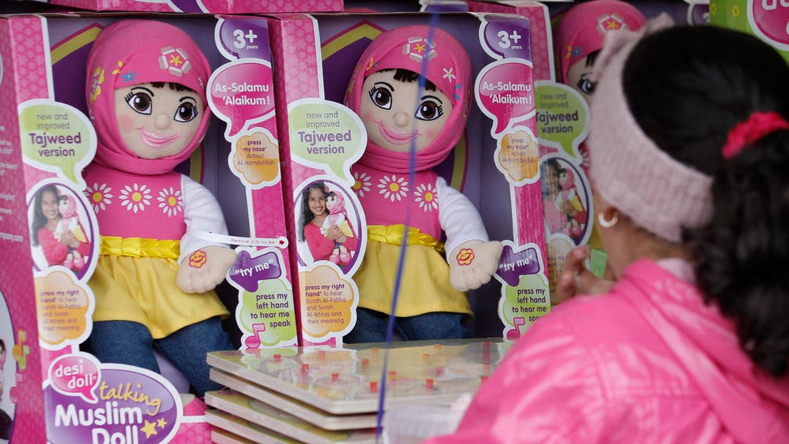 """A young girl admires talking Muslim dolls for sale on a stall at the Trafalgar Square's """"Eid in the Square"""" festival in London"""