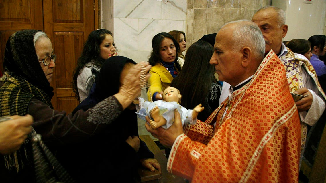 An Iraqi Christian woman crosses an effigy of baby Jesus, held by a priest, during a Christmas eve mass in a church east of Mosul, 390 km (240 miles) north of Baghdad December 24, 2010. (Reuters)
