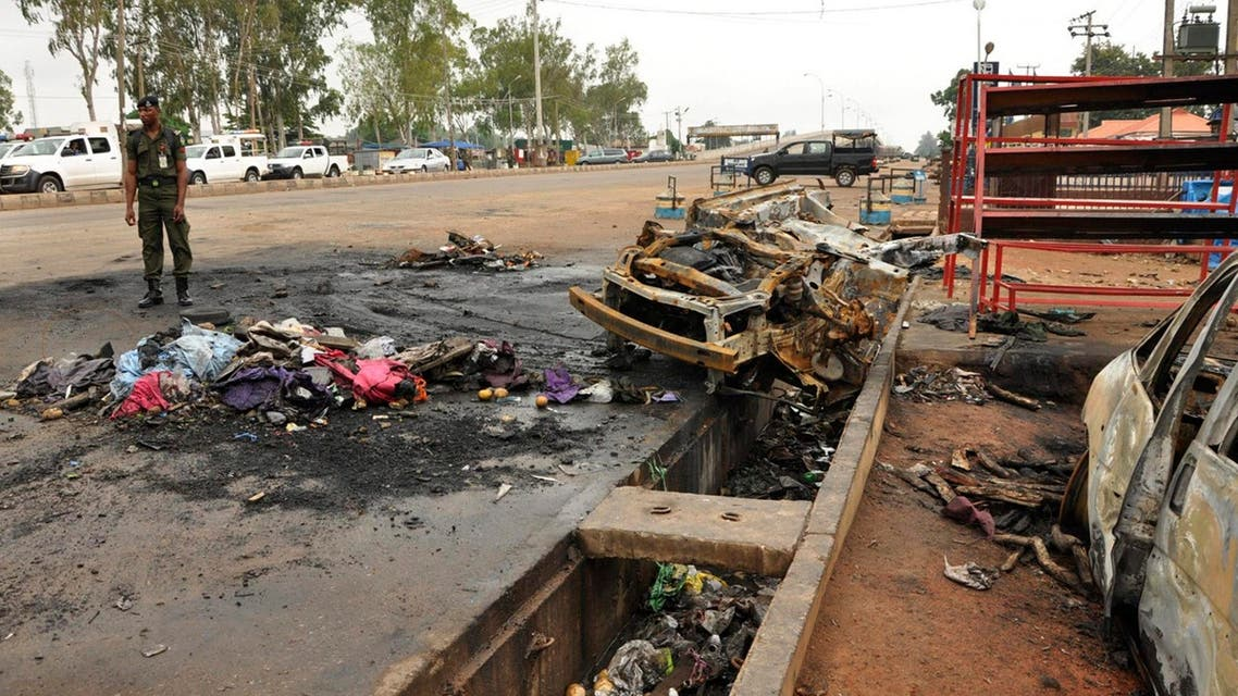 A policeman stands next to the point of impact of a suicide bomb along Alkali Road in Kaduna July 24, 2014. Reuters