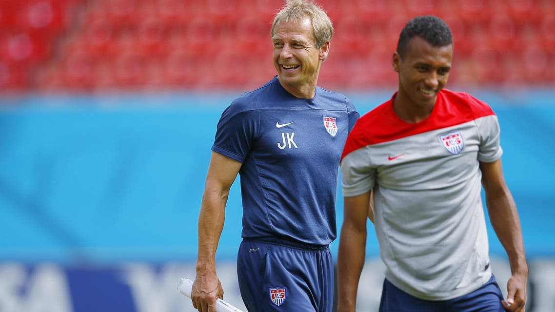 The U.S. national soccer team head coach Juergen Klinsmann (L) smiles as his team, including midfielder Julian Green, stretch during a training session at the Pernambuco arena in Recife June 25, 2014. (Reuters)