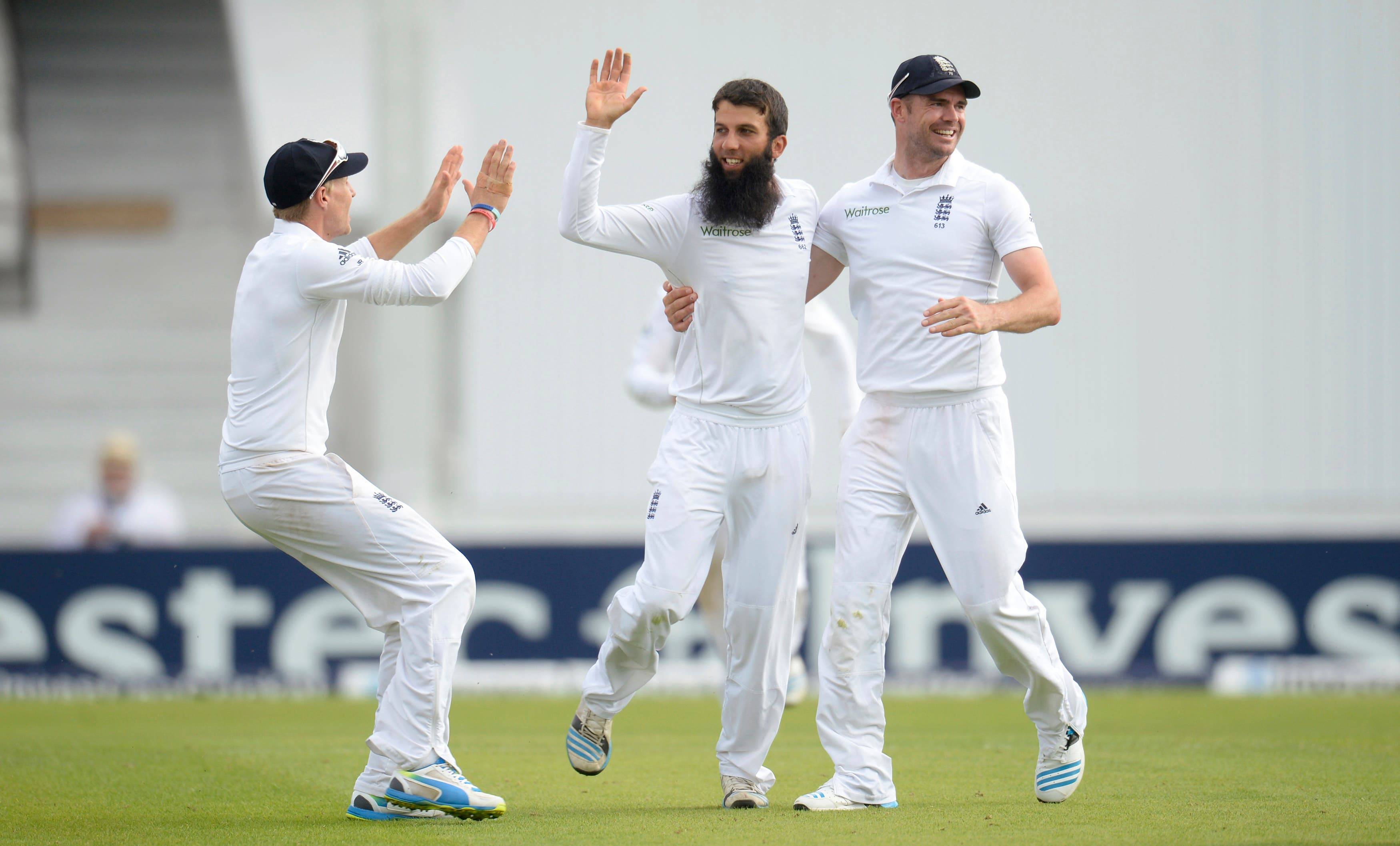 England's Moeen Ali celebrates with teammates James Anderson (R) and Joe Root (L) after dismissing Sri Lanka's Lahiru Thirimanne during the second cricket test match at Headingley cricket ground in Leeds, England June 22, 2014. (Reuters)