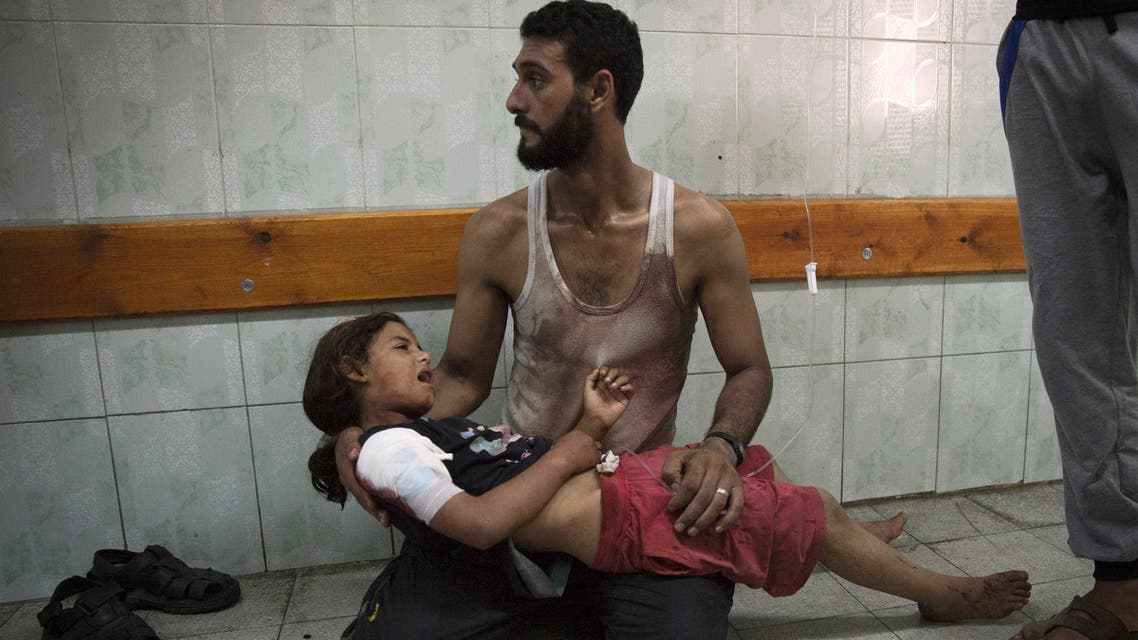 A Palestinian man holds a girl, whom medics said was injured in an Israeli shelling at a U.N-run school sheltering Palestinian refugees, at a hospital in the northern Gaza Strip July 24, 2014.