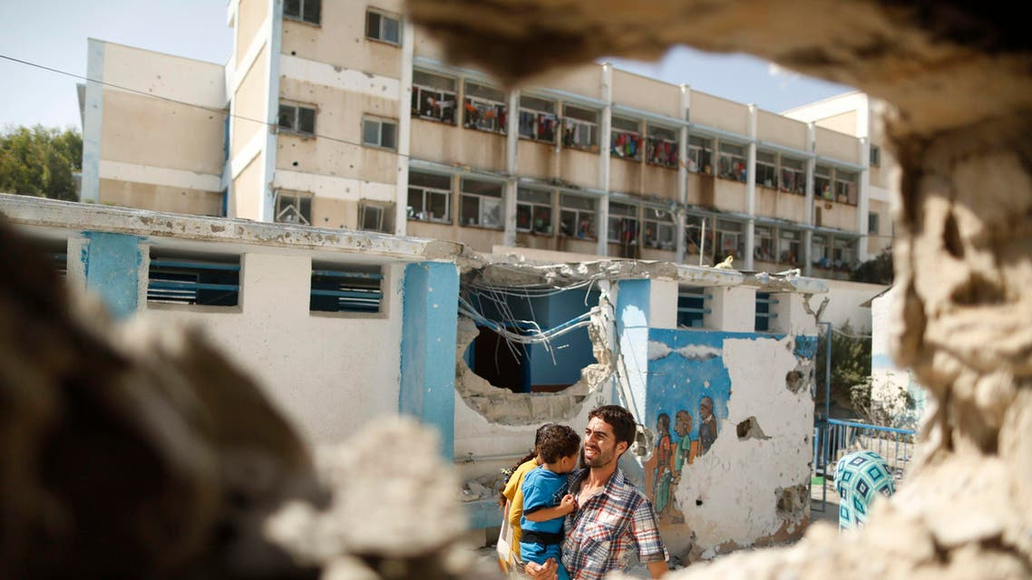 A Palestinian man pictured through a damaged classroom carries a boy as he walks at a United Nations-run school sheltering Palestinians displaced by an Israeli ground offensive. (Reuters)