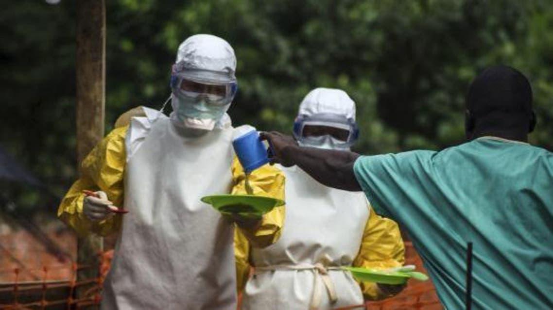 ممرضون بملابس واقية يقدمون الطعام لمريض معزول بعد اصبته بفيروس ايبولا