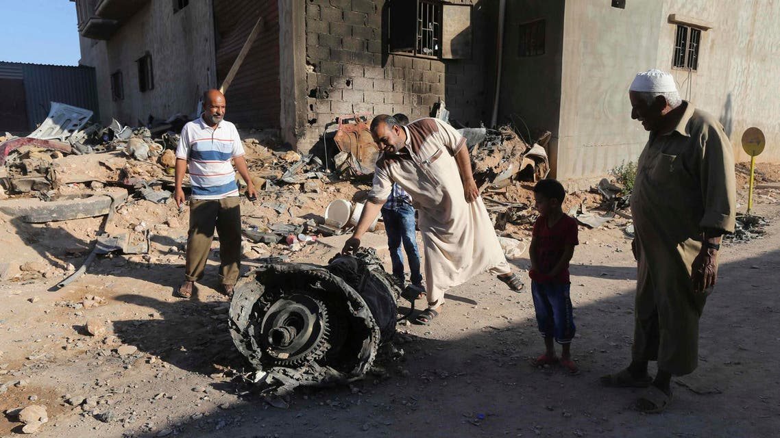 People stand next to the wreckage of a government MiG warplane which crashed during Tuesday's fighting, in Benghazi, July 29, 2014. (Reuters)