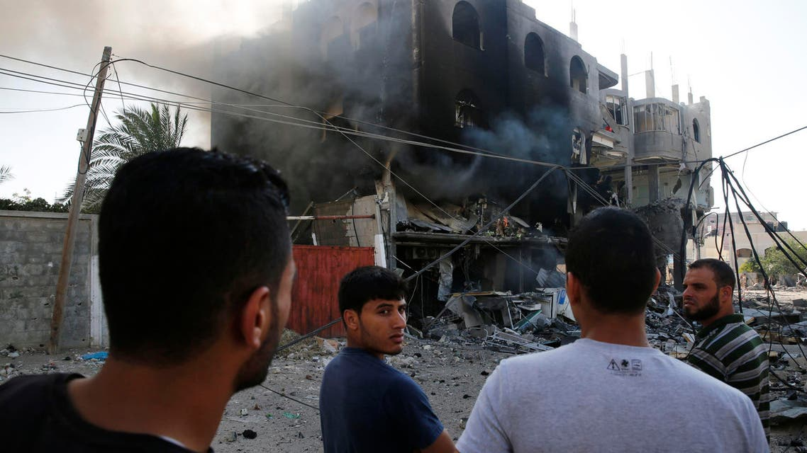 Palestinians gather near a burning building that police said was destroyed by an Israeli Air strike in Gaza City July 31, 2014.