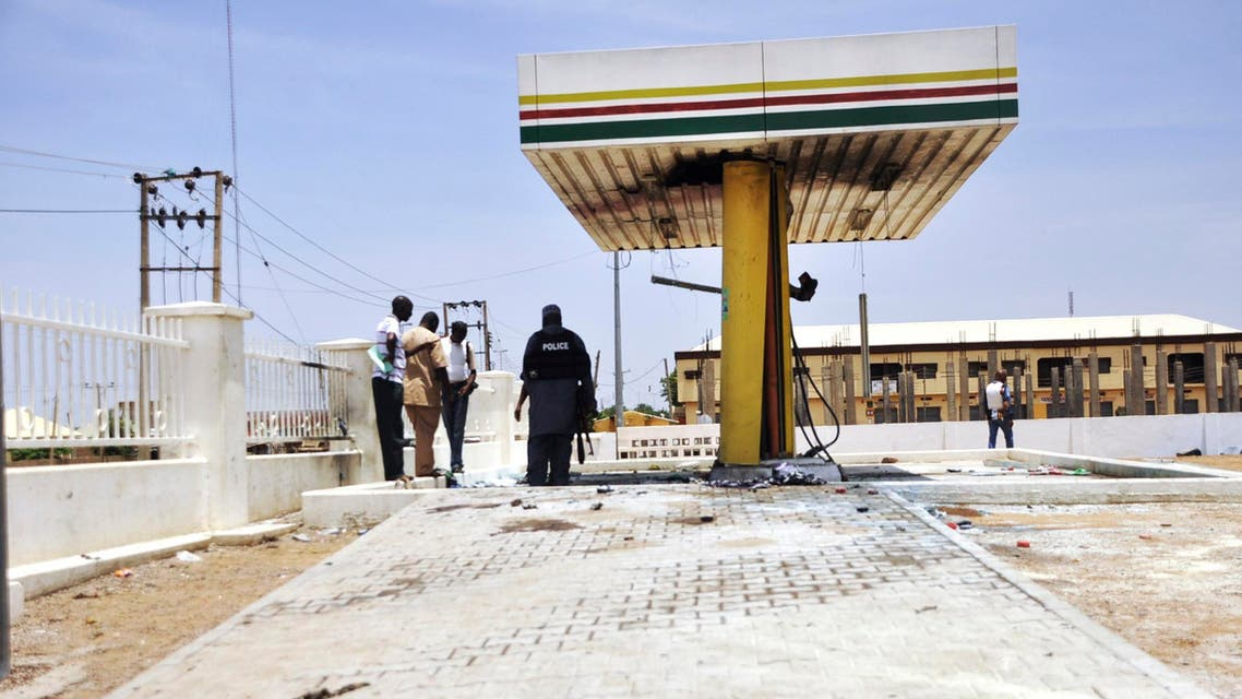 Members of the bomb squad inspect a Nigerian National Petrolium Corporation (NNPC) petrol station after a female suicide bomber blew herself in the city of Kano July 28, 2014