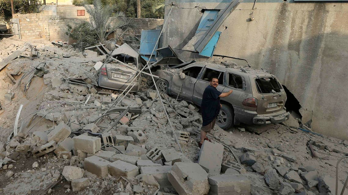 A Palestinian man speaks with a firefighter as he points to damaged cars following what witnesses said was an Israeli air strike on his house in Gaza City July 31, 2014.
