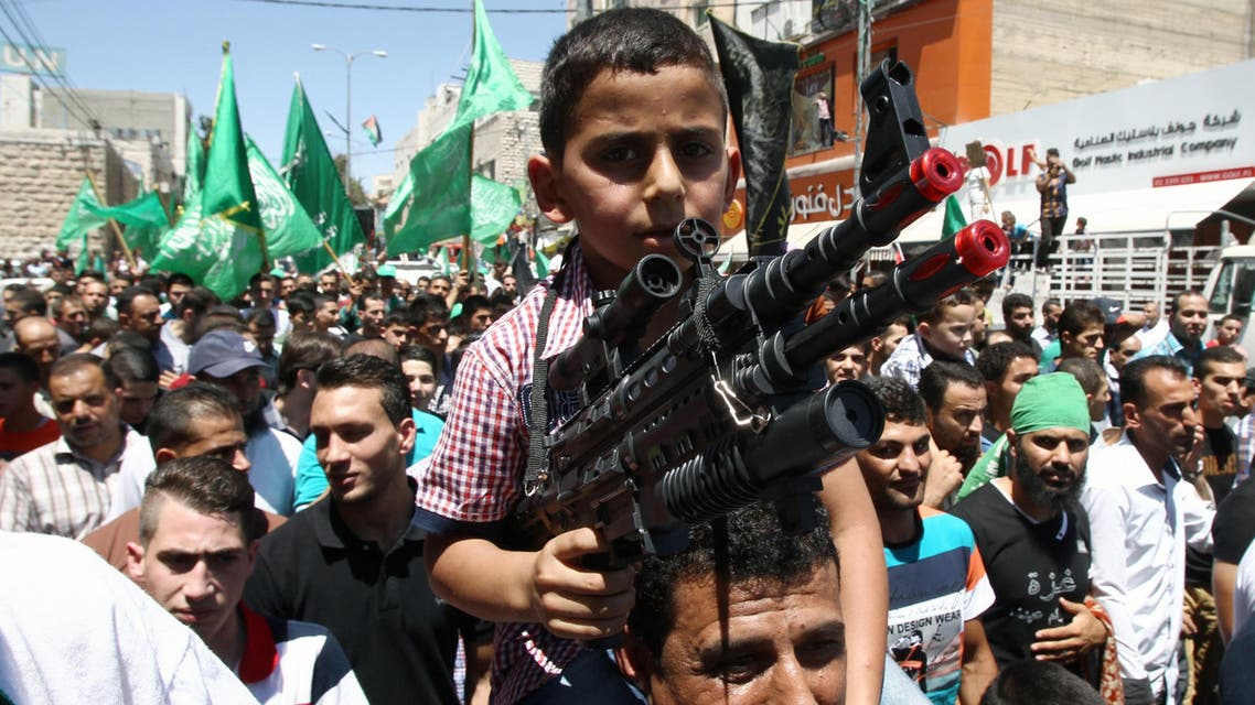 A Palestinian young boy, on his father's shoulders, holds a fake gun during a demonstration against Israel's military operation in the Gaza Strip and in support of Gaza's people on August 1, 2014. (AFP)