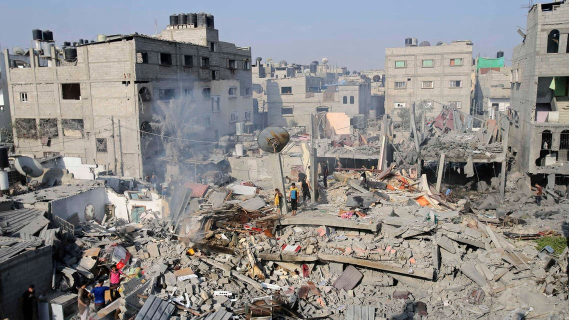 Palestinians stand atop the wreckage of a house which witnesses said was destroyed by an Israeli air strike in Rafah, in the southern Gaza Strip, August 2, 2014. (Reuters)
