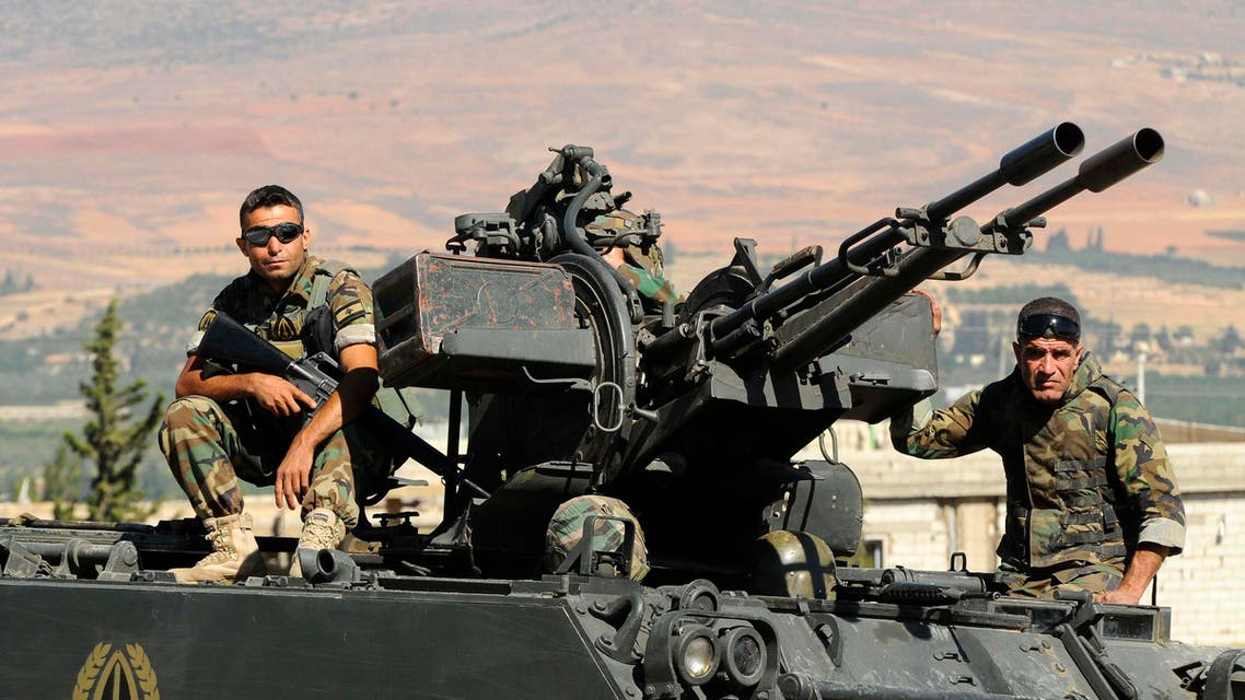 Lebanese army soldiers sit on top of an armoured vehicle near the entrance leading to Arsal August 3, 2014.