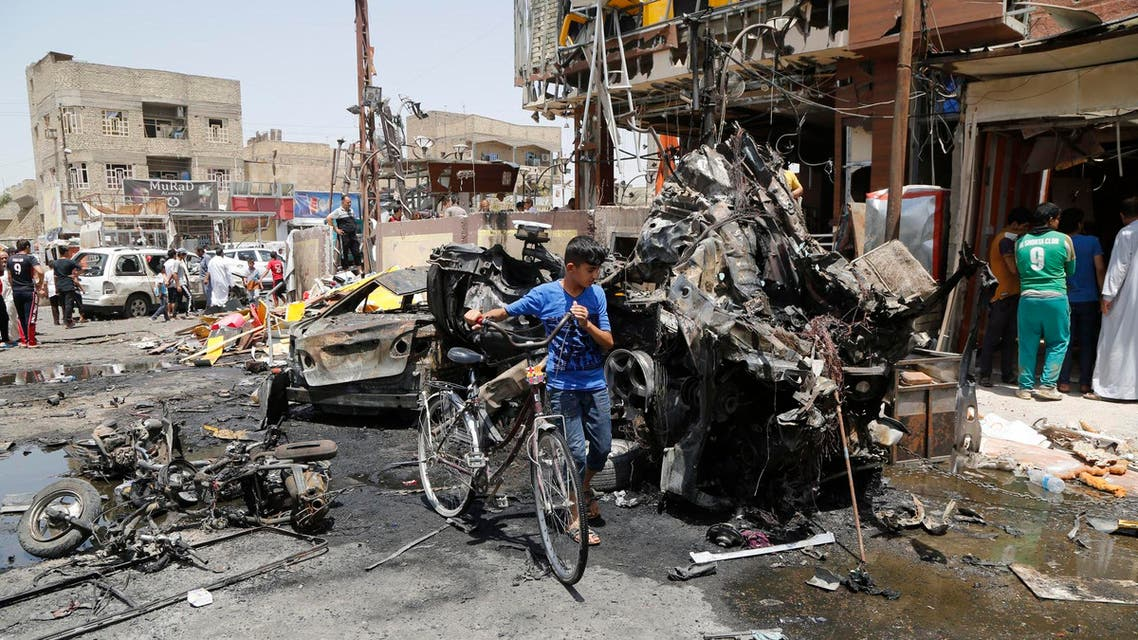 A boy walks past with his bicycle near the site of a car bomb in Baghdad's Sadr City, August 1, 2014.