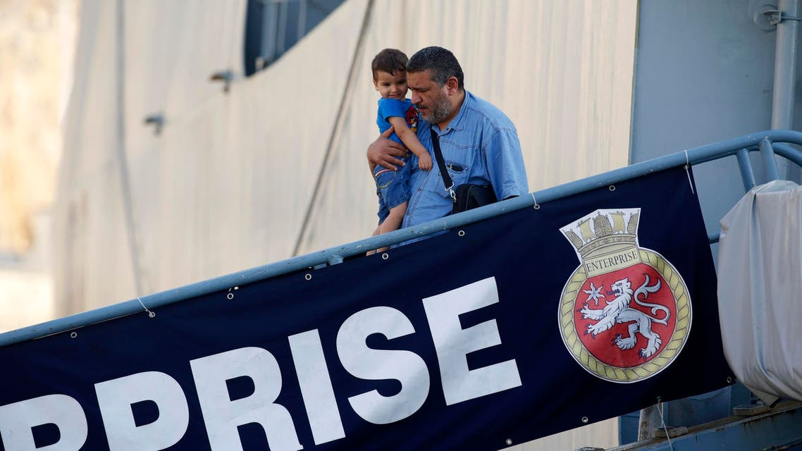 An evacuee carries his child as they disembark from the British Royal Navy ship HMS Enterprise after it arrived from Tripoli, Libya, at Valletta's Grand Harbour August 4, 2014. (Reuters)
