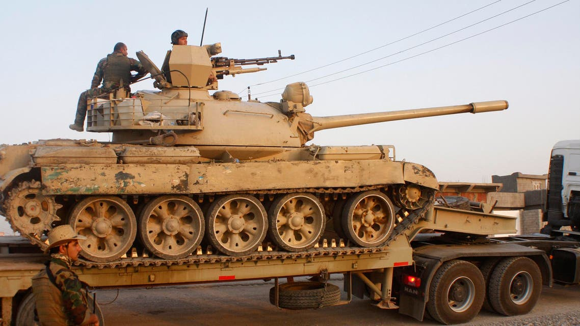 """Kurdish """"peshmerga"""" troops move down a street next to a transported tank during an intensive security deployment after clashes with ISIS militants in Jalawla, Diyala province, July 4, 2014. (Reuters)"""