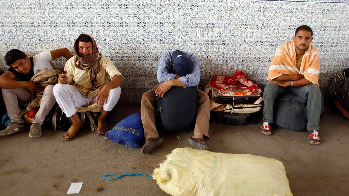 Egyptian men wait to be transported to Djerba airport, from where they will be evacuated back to Egypt, at the Ras Jdir border crossing, southeast of Tunis August 3, 2014. (Reuters)