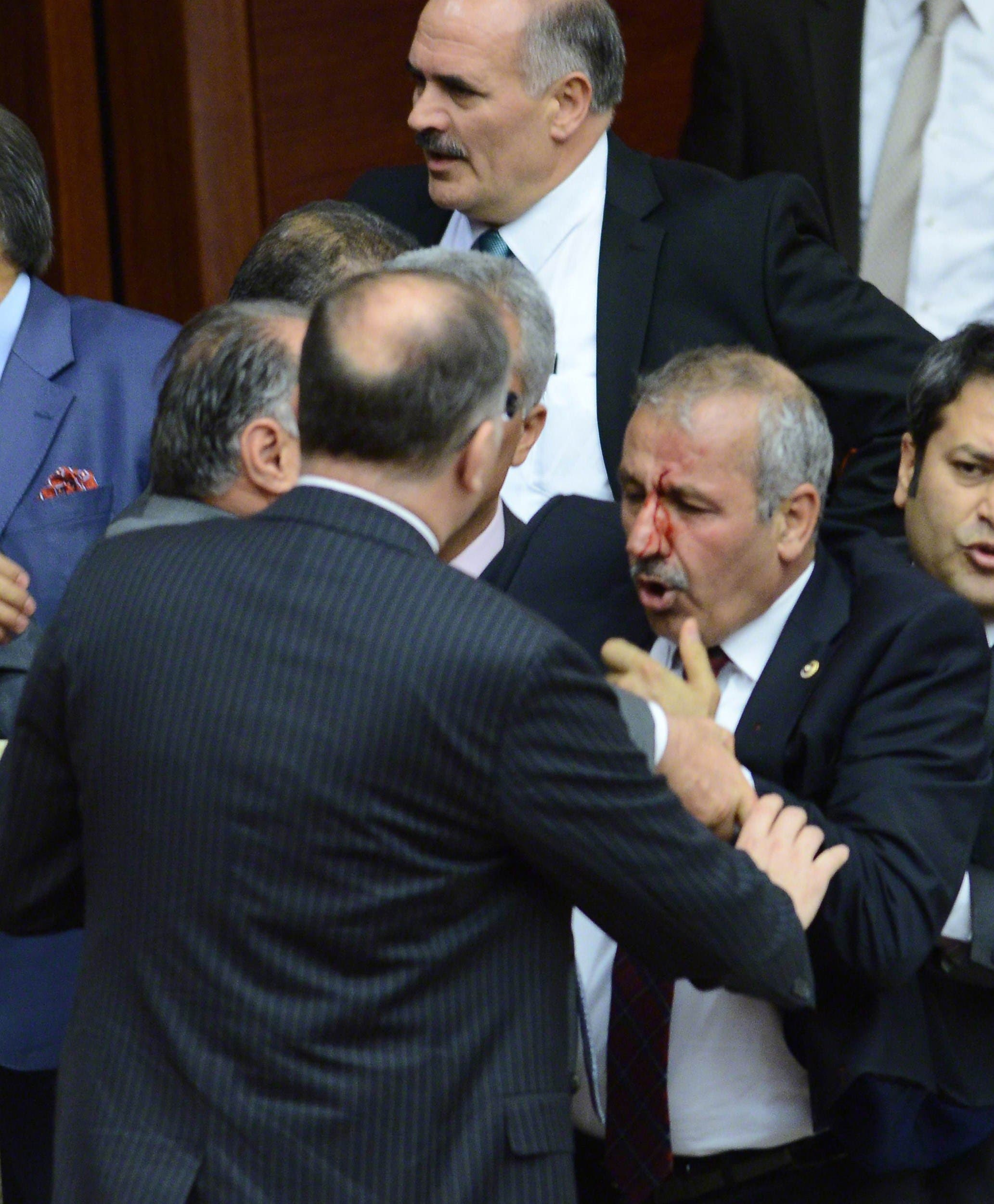 Opposition party MHP's deputy Ali Uzunirmak (R) reacts during a fight with a deputy of the AKP ruling party at the parliament in Ankara, on August 4, 2014. (AFP)