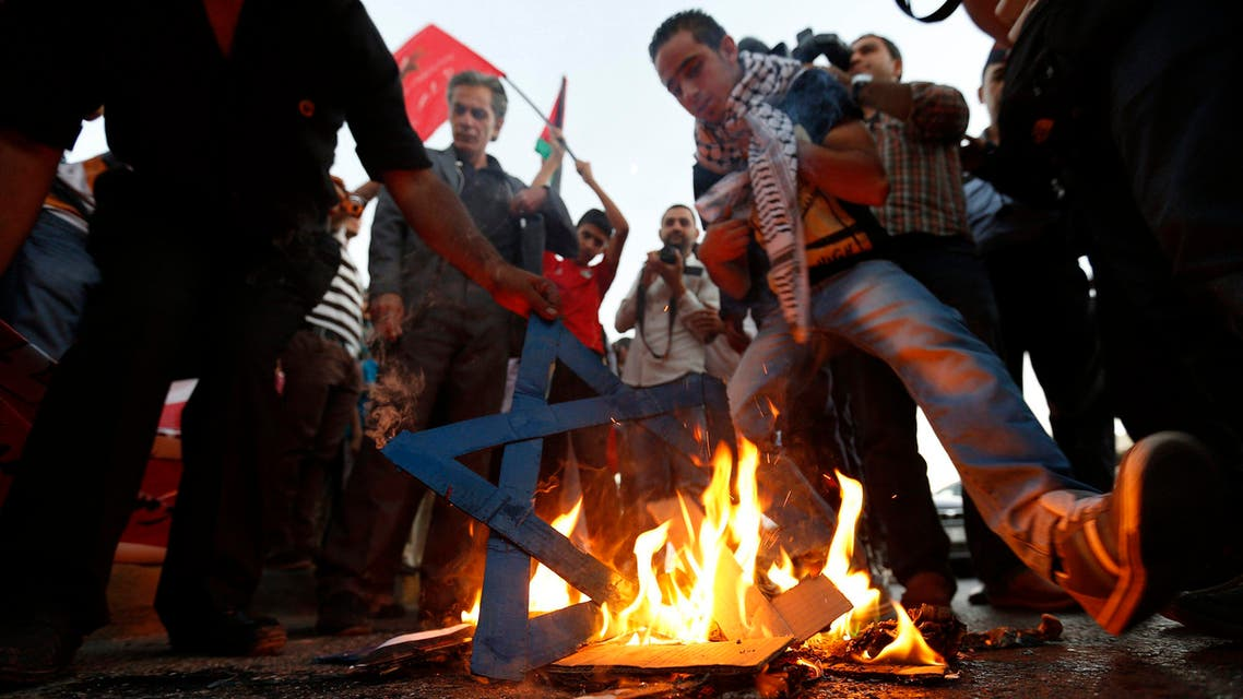 Members of Jordanian opposition parties burn a cut-out of a Star of David during a demonstration calling for an end to the Israeli offensive in the Gaza Strip, in front of the U.S. embassy in Amman August 3, 2014 reuters